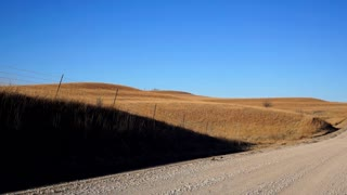 The landscape of the Flint Hills of Kansas in late winter. A Dirt Road cuts through the prairie.