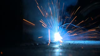 Welding Steel with sparks and electric arc in Close Up at a industrial metal fabrication shop.