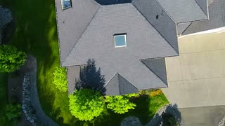 Aerial footage of an American suburban home, direct-down view as camera pulls away to show surrounding area