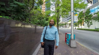 African American businessman walking along a city sidewalk