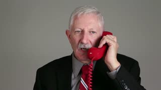 Angry old businessman shouting on the telephone