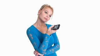 Attractive young blonde woman changing channels on a television with a remote control and a look of boredom on her face