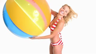 Attractive young blonde woman in red white and blue bikini playing with large beach ball