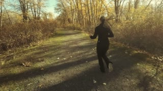 Attractive young woman jogging on a nature trail at sunset