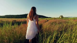Attractive young woman walking in a grassy field at dusk
