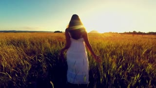 Attractive young woman walking in a grassy field at sunset