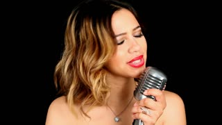Beautiful young Hispanic singer performing with a vintage chrome microphone