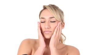 Beautiful young Hispanic woman rubbing moisturizer lotion on her face