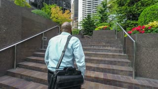 Businessman walking to work, climbing steps in front of office building