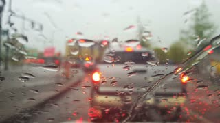 Cars waiting at a traffic light during rush hour on a rainy day, viewed through a windshield covered in water drops.