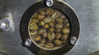 Coffee beans turning in a roasting drum as they approach first crack phase of roast.