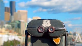 Coin operated binoculars, focus shifts from foreground to cityscape in background