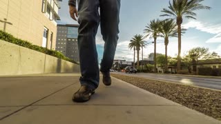 Conceptual clip of a man walking forward while the rest of the world moves backwards; closeup of feet