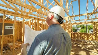 Construction worker on site with building plans, circling