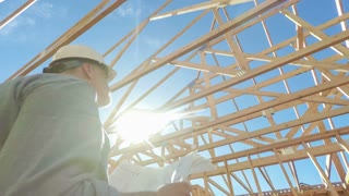Construction worker on site with building plans, low angle view