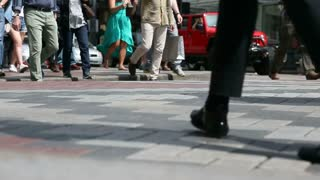 Crowd of people crossing a city crosswalk - ground level view of feet only