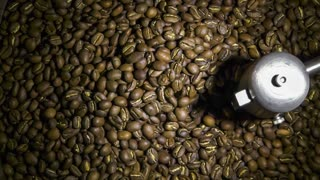 Freshly roasted coffee beans on a cooling tray, being mixed by a rotating mechanical arm, then being emptied. Slow motion footage.