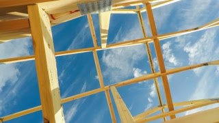 Low angle view of roof beams at a modern home construction site with blue sky and clouds in the background