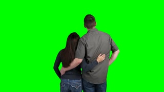 Happy couple standing close together admiring a blank green screen in front of them