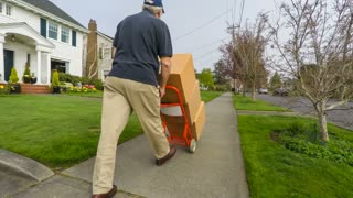 Impatient senior delivery man tosses a package carelessly onto the front porch of a suburban home