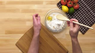 Male chef mixing ingredients in a glass bowl on top of a butcher block kitchen counter