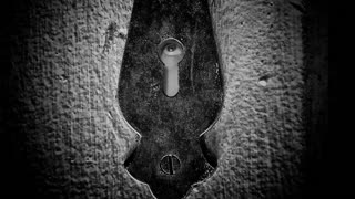 Male eye looking around through a keyhole of a vintage door