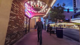 Man walks along a city sidewalk at night illuminated by casino lights as everything around him moves in reverse