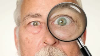 Old man looking through magnifying glass