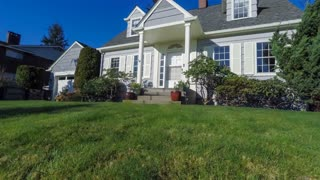 Quaint American Cape Cod style house on a sunny day with green grass and blue sky; jib shot.