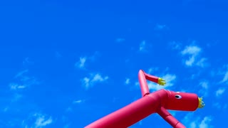 Red air dancer dancing against a blue sky