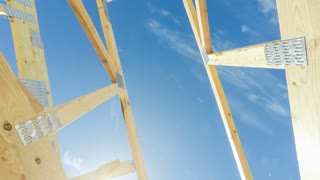 Rotating low angle view of roof beams at a modern home construction site with blue sky and clouds in the background