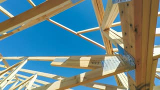 Rotating low angle view of roof beams at a modern home construction site with blue sky and sunlight in the background