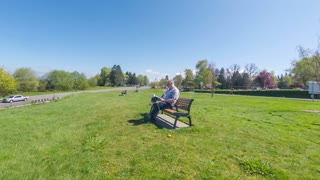 Senior adult male sitting on a park bench reading a book experiences back pain when standing