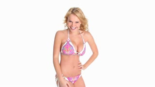 Sexy young blonde woman in pink paisley bikini flirting with the camera