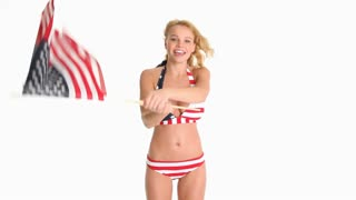 Sexy young blonde woman in red white and blue bikini dancing with two American flags