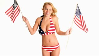 Sexy young blonde woman in star-spangled bikini dancing with two American flags
