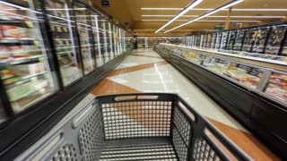 Shopping cart moving down a supermarket isle