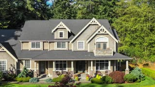 4k footage of a modern European style luxury craftsman home; aerial approach