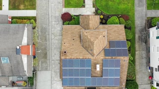 Aerial view of a suburban home rooftop with solar panels; rising altitude