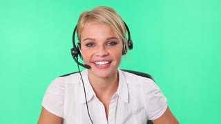 Attractive young female customer service agent talking to a customer with a telephony headset