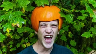 Creepy man laughing with missing teeth while wearing a pumpkin helmet for Halloween