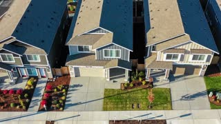Flying over a row of houses in an American suburban neighborhood. New construction houses for sale.