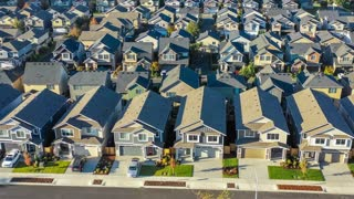 Flying over an American suburban neighborhood with small craftsman style houses