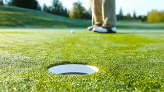 Golfer on putting green misses the cup