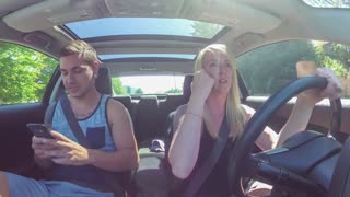 Playful young couple in car; boyfriend snatches smartphone from girlfriend as she starts to text while driving then offers her a bite of beef jerky
