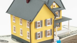 Toy model home sitting on top of a stack of 100 dollar bills USD, held in the palm of an adult male hand; HD ProRes clip