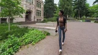 Young African American college student walking on campus as she listens music on