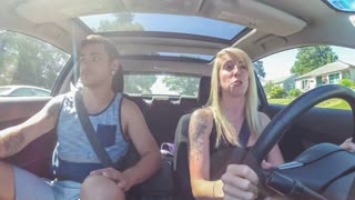 Young couple in car; boyfriend snatches smartphone from girlfriend as she starts to text while driving