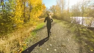 Young woman running on a nature trail in the fall