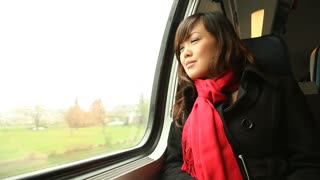 Young Asian woman riding a passenger train looking out the window